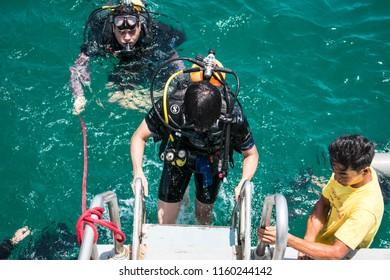 Thailand - 16 August 2018 : A diver climb up a ladder after diving at Chonburi, Thaialnd