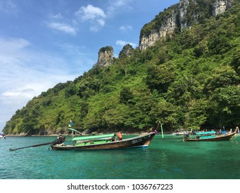 thailand 2018-wooden boat waiting for customer snorkeling near phanga island at krabi.background with mountain and blue sky