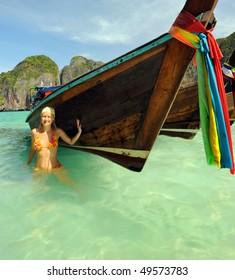 Thailand. Andaman sea. Ko Phi Phi Leh island. Maya bay. Colorful tropical landscape and a smiling girl in orange swimsuit near wooden thai boat