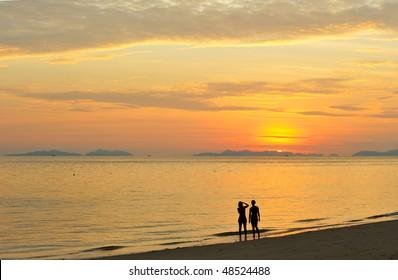 Thailand. Andaman sea. Phi Phi island. Magic sunrise landscape and silhouettes of two girls making photos