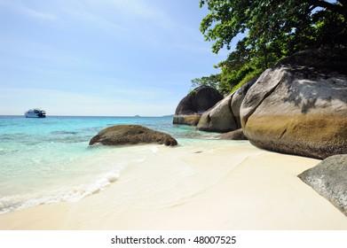 Thailand. Andaman sea. Similan islands. Sand beach, calm blue sea, splendid green, big stones and diving boat