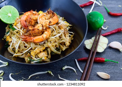 "Thailand or asia food Fried rice Noodles and shrimp ""Pad Thai""with and vegetables in black dish on background."
