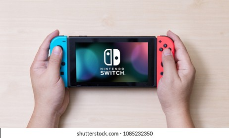 Thailand , Bangkok - MAY 7, 2018 A man holding a Nintendo Switch game console.