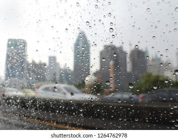 Thailand, Bangkok - November 2018: Rain drops in the car window with building in the background