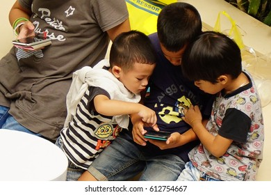 Thailand, Bangkok October 23, 2016: One girl and 3 boys gathered and looked at the smartphone, this device is the favorite item for everyone.