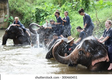 THAILAND, CHIANG MAI, 27 JULY 2011 - Happy people have fun with elephants making splashes with their trunks in river, Chiang Mai, Thailand