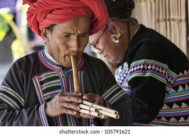 Thailand, Chiang Mai, Karen Long Neck hill tribe village (Kayan Lahwi), Karen man in traditional costumes playing a flute
