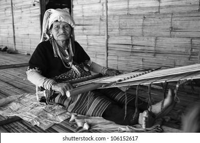 Thailand, Chiang Mai, Karen Long Neck hill tribe village (Kayan Lahwi), a Karen woman in traditional costumes is making a carpet