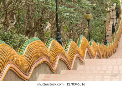 Thailand, Chiang Mai Province, Wat Phra That Doi Suthep. Steps to the temple with dragon decorations along the sides.
