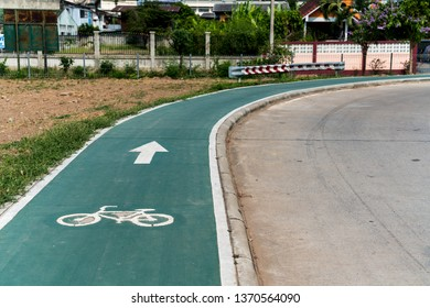 In Thailand in a city is this beautiful green bike path with arrow