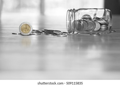 Thailand coins in a glass jar on a wooden floor.