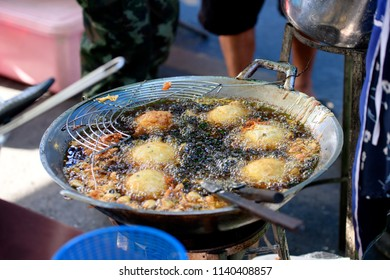 Thailand country local desserts using the dough balls round frying pan in a tricky market