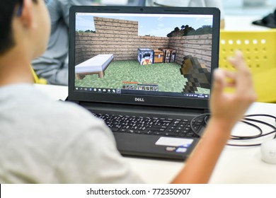 Thailand, December, 2017. The young Asian boy is creating his land by the minecraft creation the most favorite game for young child in the coding for kids classroom in Thailand.