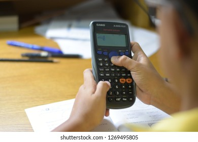 Thailand, December 2018. The young Asian boy is solving his mathematics problem homework by using the calculator at home in Thailand.