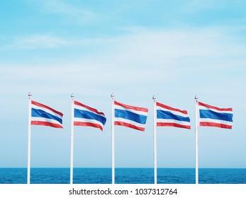 Thailand flag over beach and blue sky background.