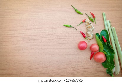 Thailand Food Ingredients: Kaffir lime leaves,tomato,chilli,galangal,lemon grass on wood background. Thai food cooking ingredients.Example Tomyam soup.