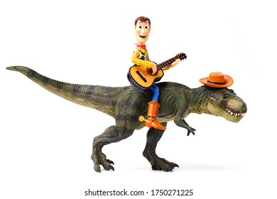 Thailand -June 6, 2020: Woody figure model. Woody plays the guitar on back dinosaur. Feeling relax and fresh.This figure by disney Pixar inc.