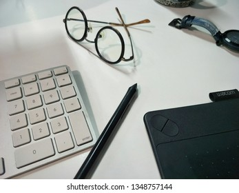 Thailand -March 25, 2019 : Office room Building,Keyboard and wacom pen with eyeglass on table