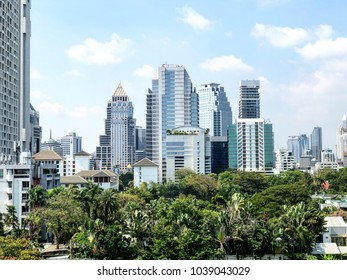 ?Bangkok, Thailand - March 5, 2018: The cityscape view of smart buildings in Bangkok against the blue sky with the green natural area of trees in central Bangkok, Thailand.