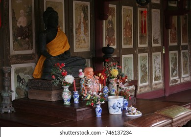 THAILAND, MAY 01, 2008:Buddha placed on the table for worship. Flowers and incense sticks are placed. The backdrop is an ancient drawing that tells tales in Buddhism.