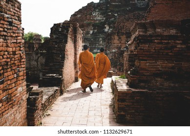 Thailand monks, group of young friends walking trough historical city. Old town made of bricks, which are ruins now, named Ayutthaya.