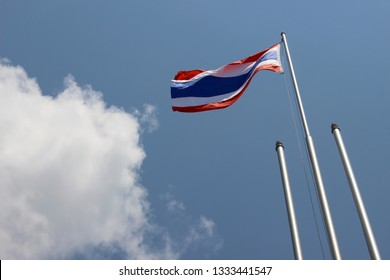 Thailand National Flag Flying on Flagpole Against Blue Sky and Clouds Background