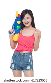 Thailand New year concept. Focus on toy gun. Young happy beauty Asian woman holding plastic water gun at Songkran festival, Thailand. Isolated on white background.