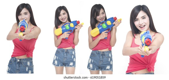 Thailand New year concept. Focus on toy gun. Young happy beauty Asian woman holding plastic water gun at Songkran festival, Thailand Isolated on white background.
