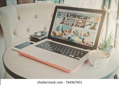 Thailand - November 29, 2017: Woman with MacBook and iPhone with social networking service Shutterstock on the screen. MacBook and iPhone was created and developed by the Apple inc
