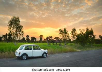 THAILAND - OCT 7, 2014 : Classic Mini Cooper and sunset over Tungkula rice fields