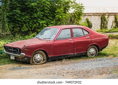 Thailand on November 5, 2016 owners of vintage red car parked flat tire ruined house in a classic car lot.
