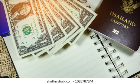 Thailand passport against dollar for every day shopping,One dollar banknote is on wood floor,Money of America