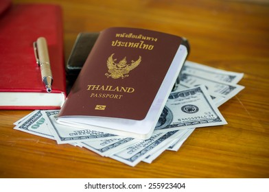 Thailand passport laying atop a pile of American dollars.Note book.