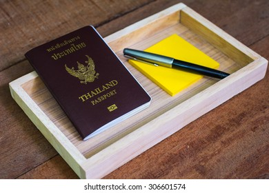A Thailand Passport, A note, and A pen in A Wooden Box with Selective Focus