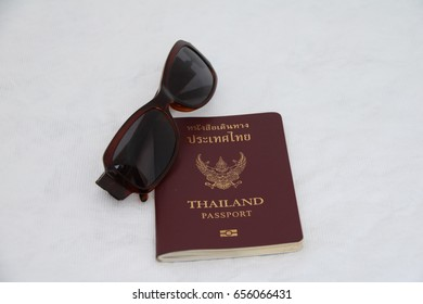 Thailand passport and sunglasses isolate on white background. Garuda on the center is symbolic of Thai government.