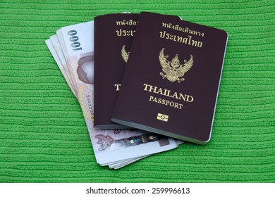 Thailand passport and Thai money isolated on green background
