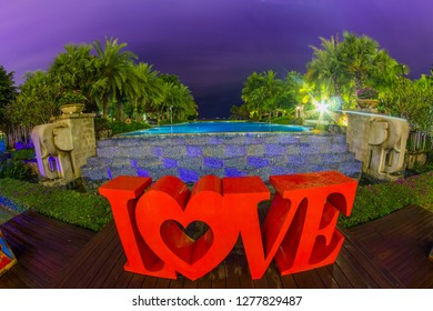 Thailand , Pattaya - January 1, 2019. Celebration of St. Valentine's Day on the tropical islands. luxury vacation. Inscription love and night lights on the background of exotic palms and night sky