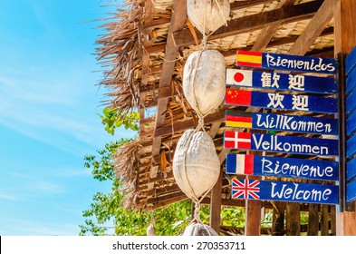 THAILAND, PHI PHI ISLANDS - NOVEMBER 1, 2014: Welcome sign in different languages with a beach in background