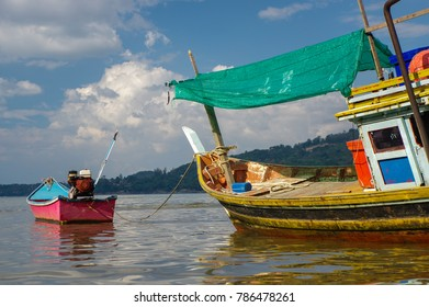 THAILAND, PHUKET, ASIA - JANUARY 28, 2016: Thai old fishing small boat at low tide in the shallows.