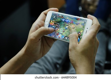 THAILAND, ROIET - MAY 22, 2017 Man playing Garena RoV Mobile MOBA game app on iPhone 7.