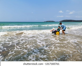 Thailand sea beach in summer, Asian special child on wheelchair is looking at sea and his father helped him to get closer to nature,Life in the education age of disabled children,Happy disabled kid.