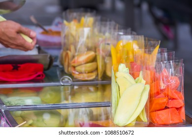 Thailand street food fruits in plastic bag ready for sale,Fresh mango, lovelorn and fruits slices in plastic bags, in a glass cabinet with ice at street market that Select focus.
