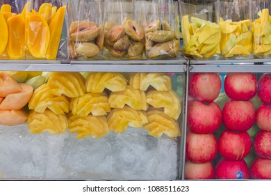 Thailand street food fruits in plastic bag ready for sale,Fresh mango,cantaloupe,lovelorn, pineapple, apples and fruits slices in plastic bags, in a glass cabinet with ice at street market.