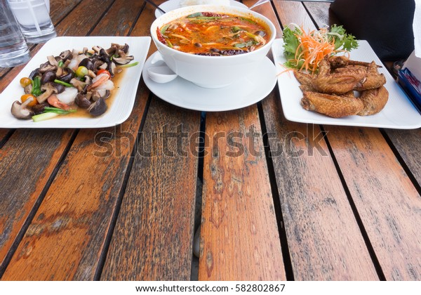 Thailand : Tom yum, chicken wing fried and fried mushroom on wooden table