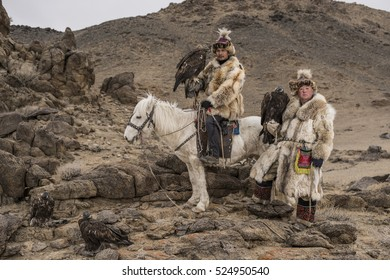 Thailand tourist in Mongolia traditionally riding horse with Kazakh Eagle Hunter in a desert mountain. Ol-gei,Western Mongolia.