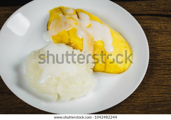 Thailand Traditional Sweet and Delicious Dessert, Sticky Rice with Fresh Sweet Mango Topping with Coconut Milk on White Plate and Dark Wooden on Black Background