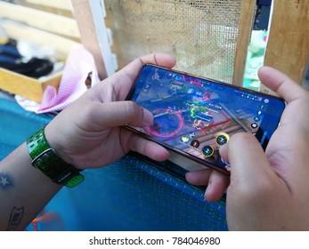 Thailand, ubon ratchathani- December 30, 2017 Man playing Garena RoV Mobile MOBA game app on Huawei mate 9.