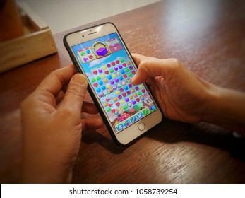 Thailand, ubon ratchathani- March 24, 2018 Women playing Candy crush Mobile game app on iphone7 plus,defocus.