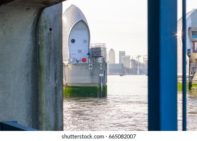 Thames Barrier with Canary Wharf in the background framed by a riverside viewing platform in London