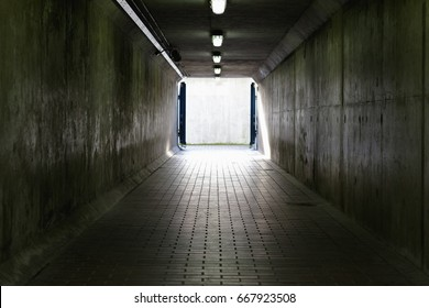 Thames Barrier passageway in London, a dim and concrete corridor leading to bright exit
